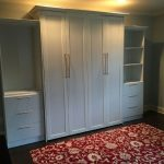 Queen Sized Murphy Bed with raised panels and custom bookcases and drawers.